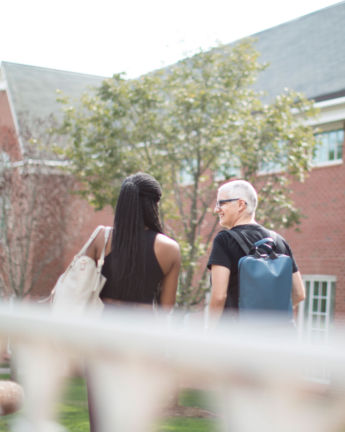 Professor Margarita Diaz walks with a student outside the Center for Communications and Engineering building