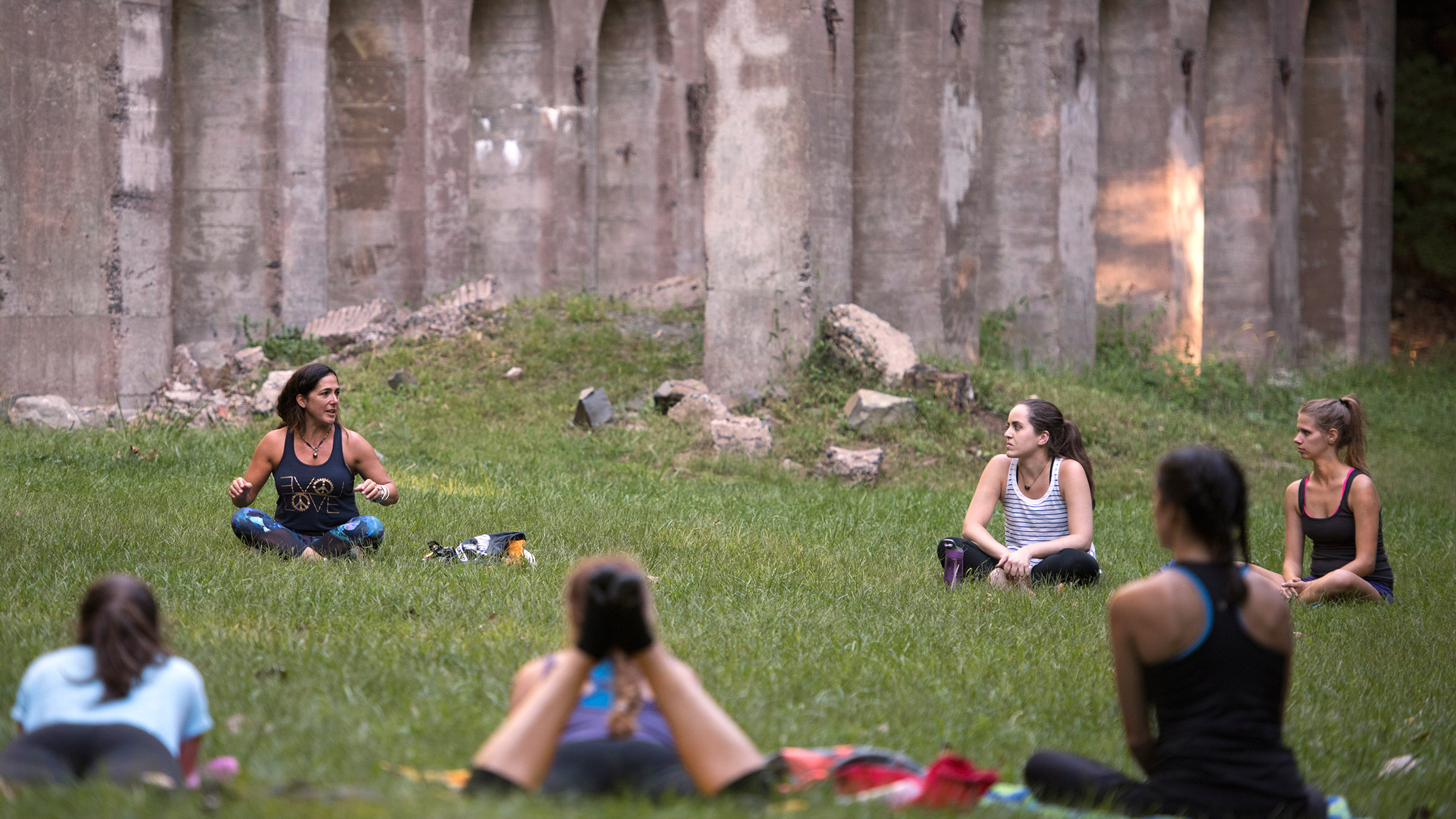 Yoga participants sit cross-legged in a circle in the grass beside the Sleeping Giant castle