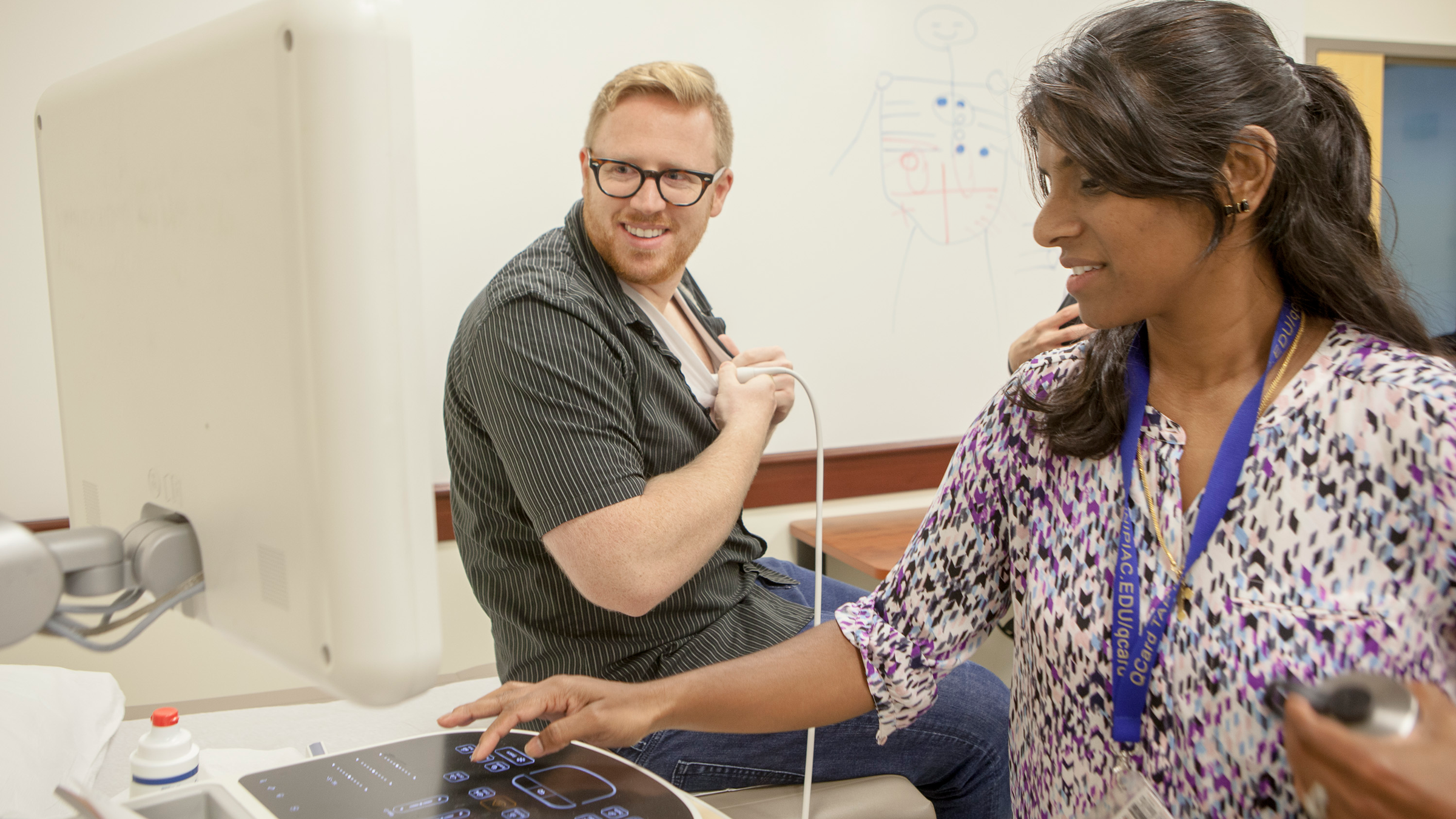Dr. Professor Listy Thomas, right, instructs Cameron Harrison MD '17 in sonogram techniques in the Center for Medicine, Nursing and Health Sciences. Thomas has been developing an interdisciplinary ultrasound curriculum with the School of Health Sciences.